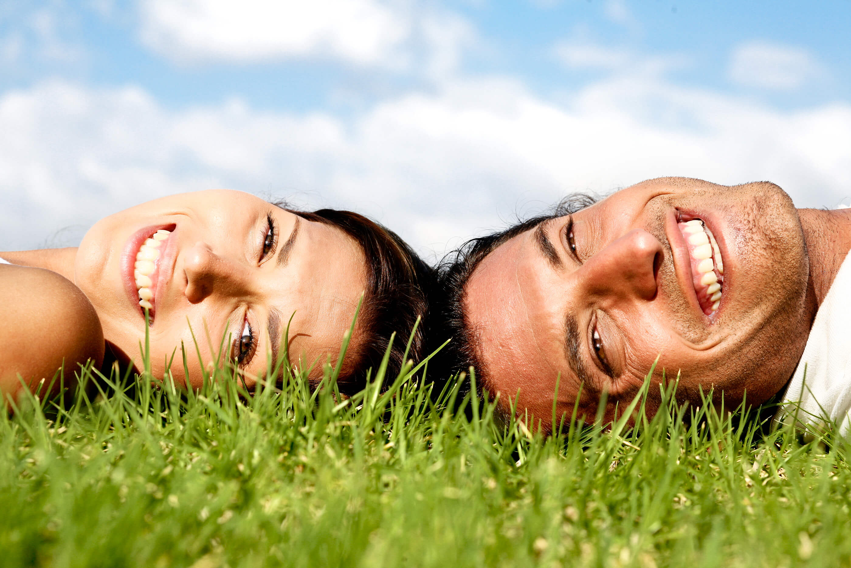 Smiling couple lying on grass and relaxing