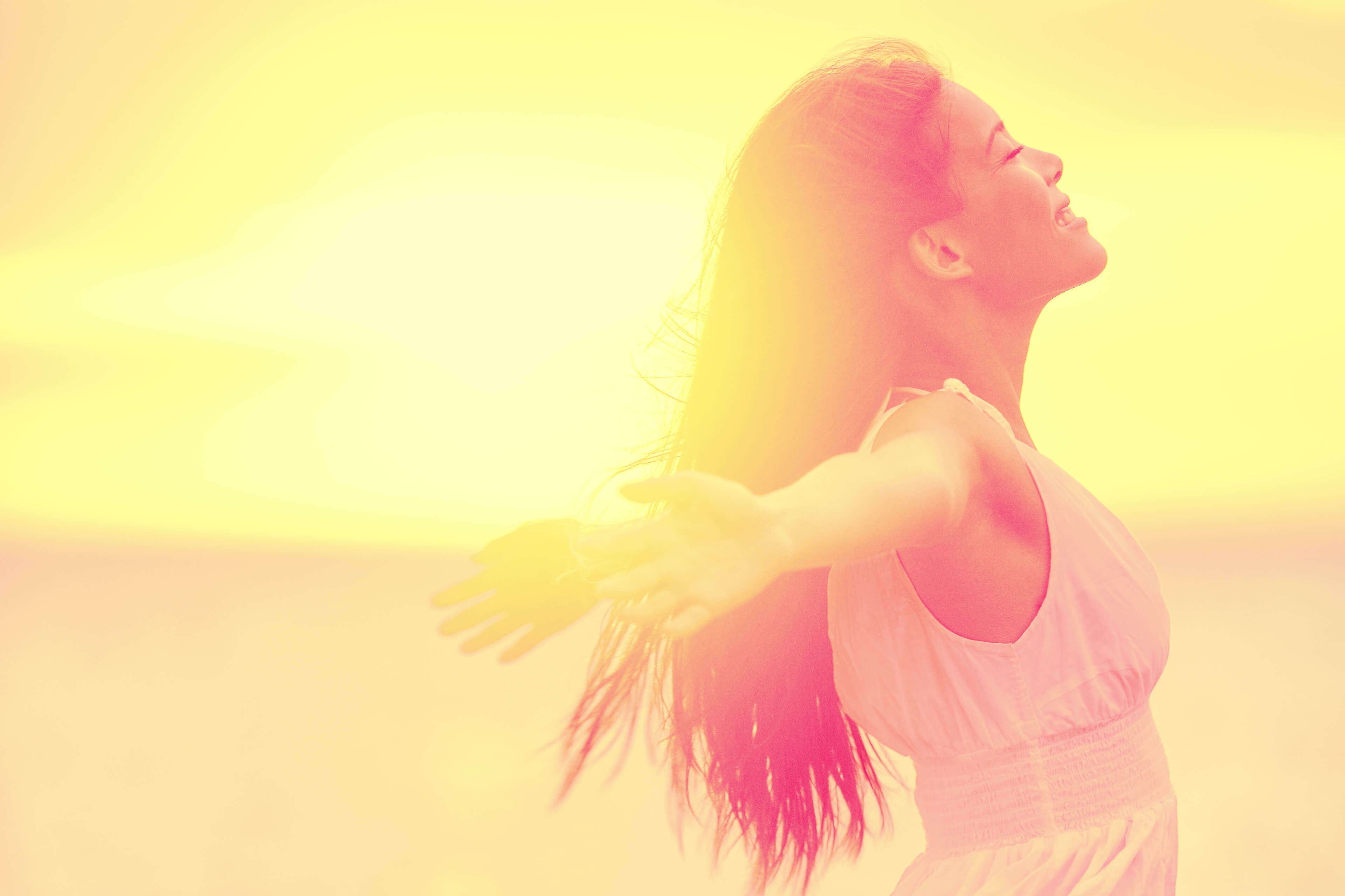 Happiness - Free happy woman enjoying sunset. Beautiful woman in white dress embracing the golden sunshine glow of sunset with arms outspread and face raised in sky enjoying peace, serenity in nature