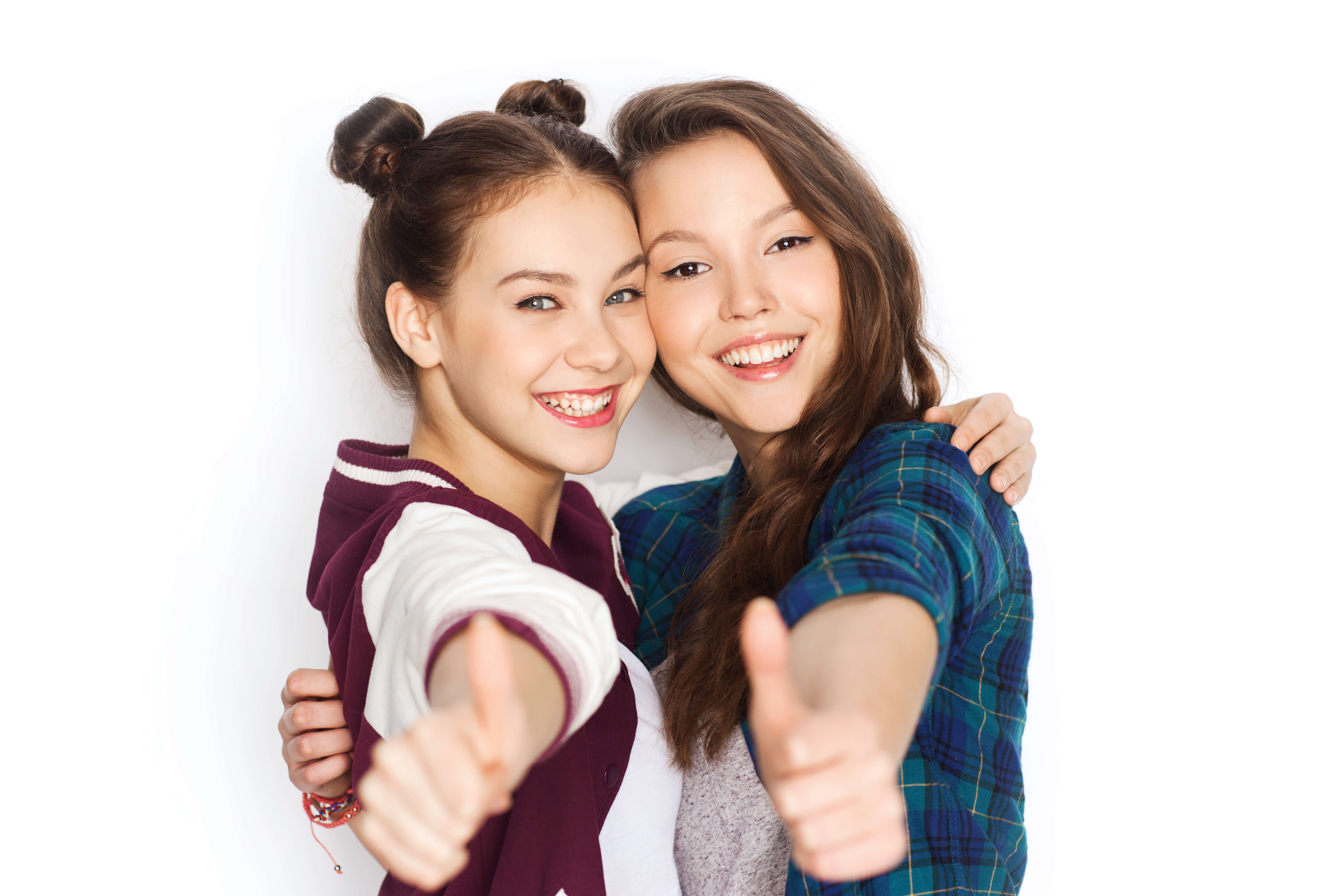 people, friends, teens and friendship concept - happy smiling pretty teenage girls hugging and showing thumbs up