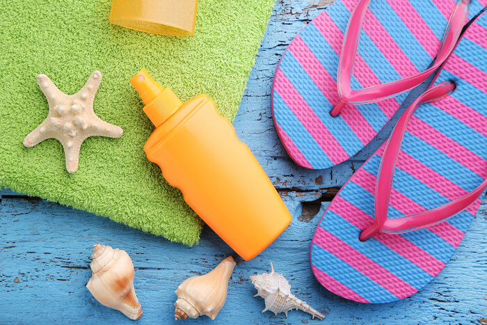 Sunscreen with flip flop and seashells on blue wooden table